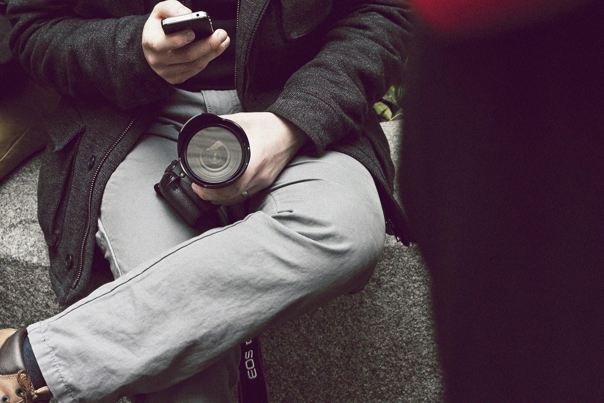 Man holding a camera, staring at his phone