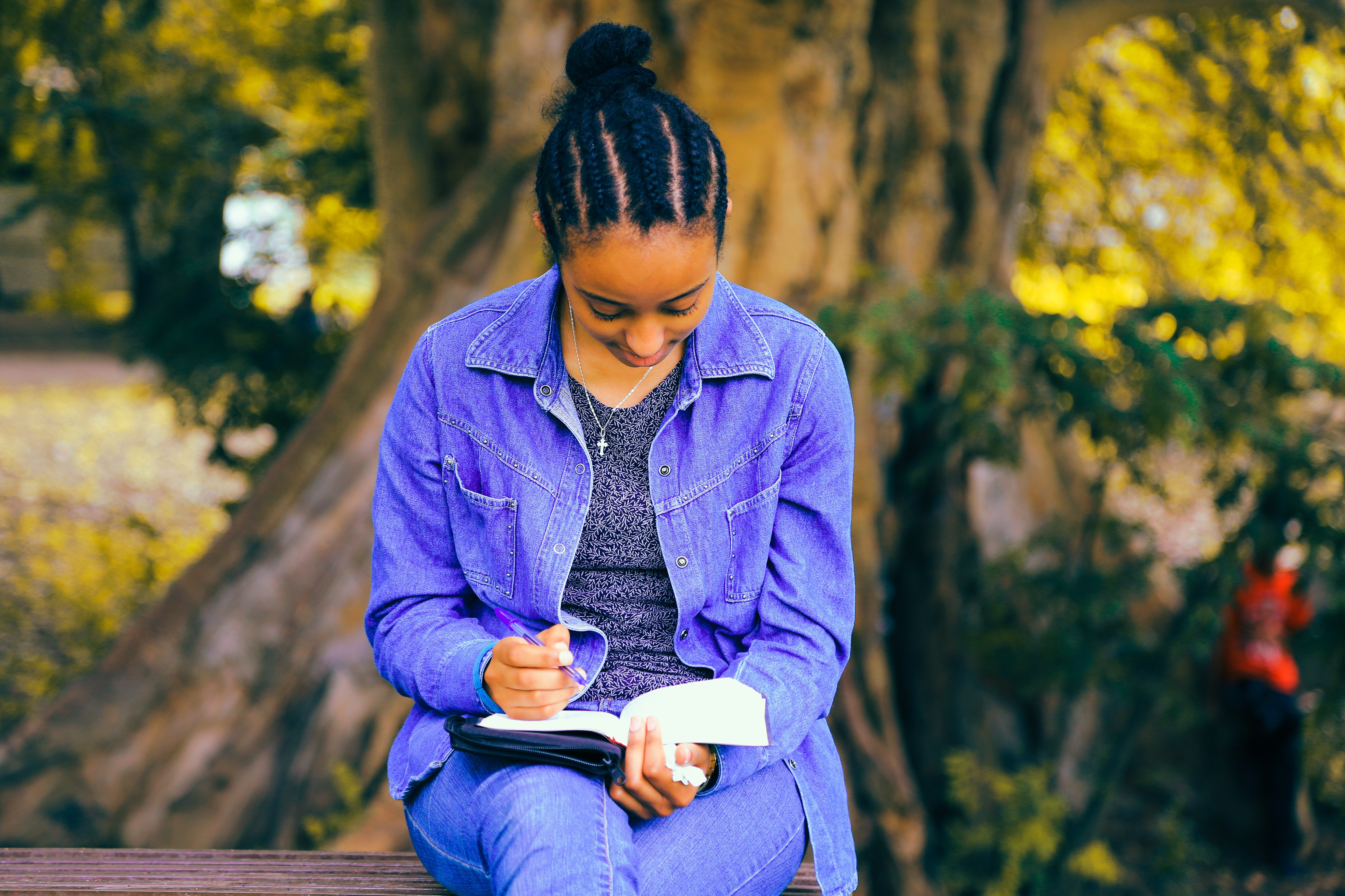 Girl sitting outside, reading the bible while holding a pen