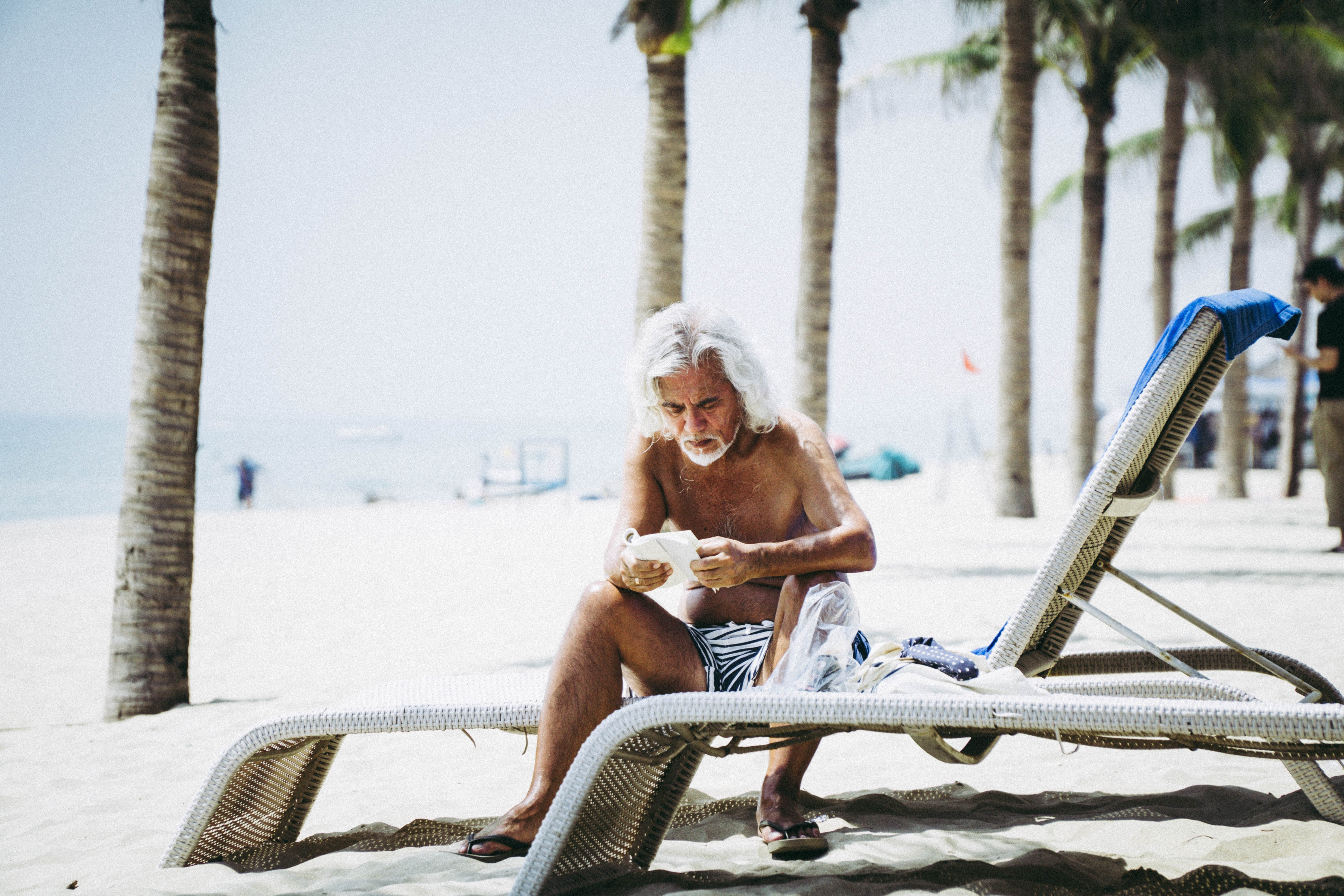 Old man, sitting near the sea. Reading a book